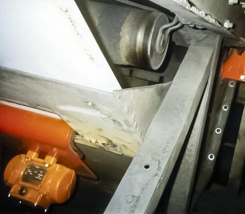 Vibrating subfloor prevents build-up in conveyor discharge